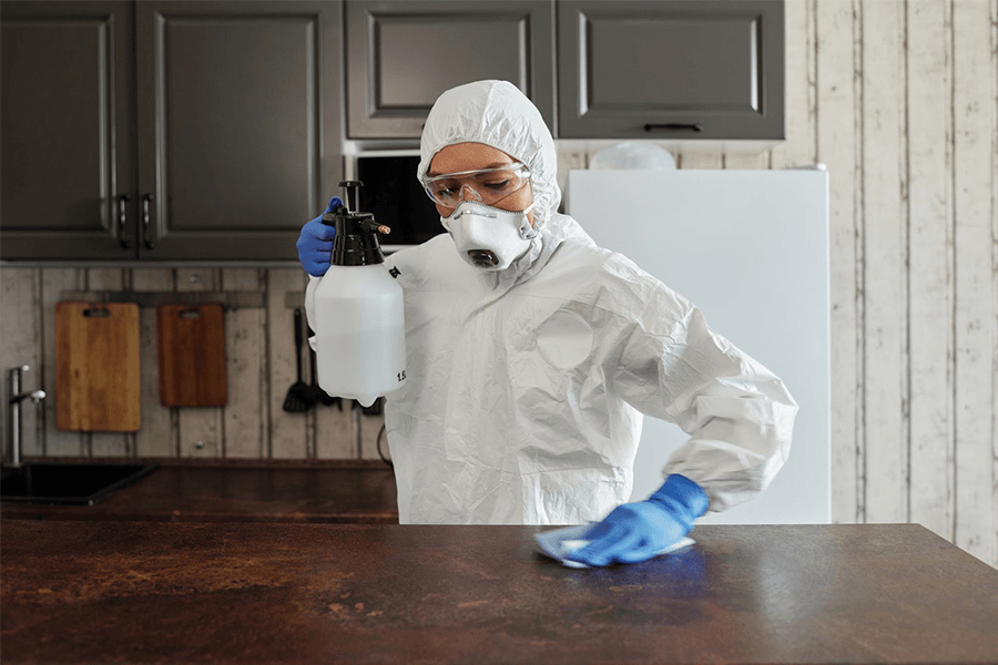 Person in protective suit disinfecting the table
