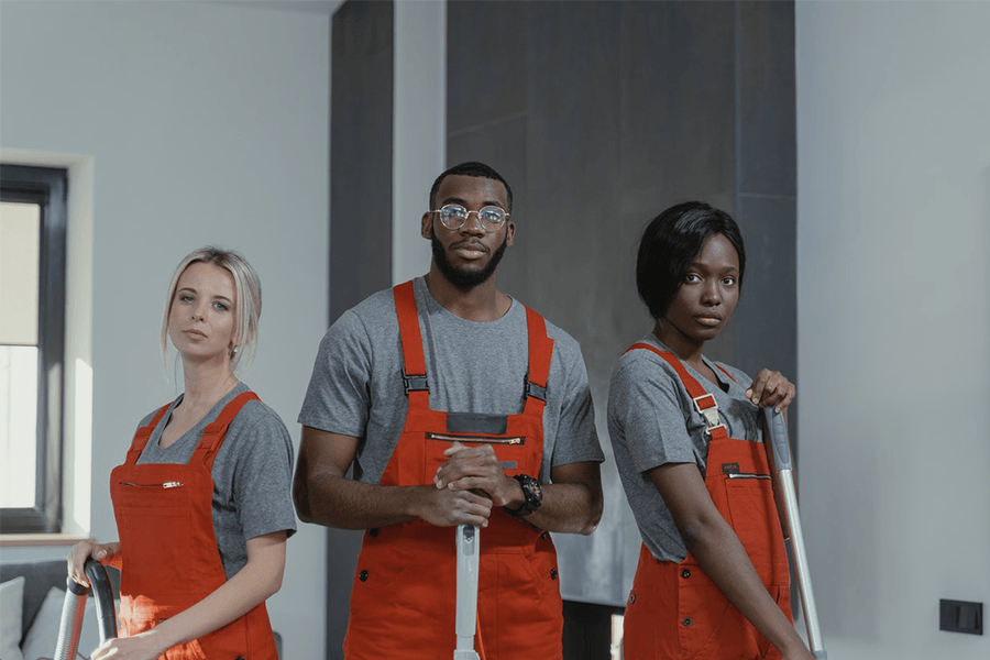 3 persons in orange overalls and grey t-shirts standing side-by-side holding cleaning supplies