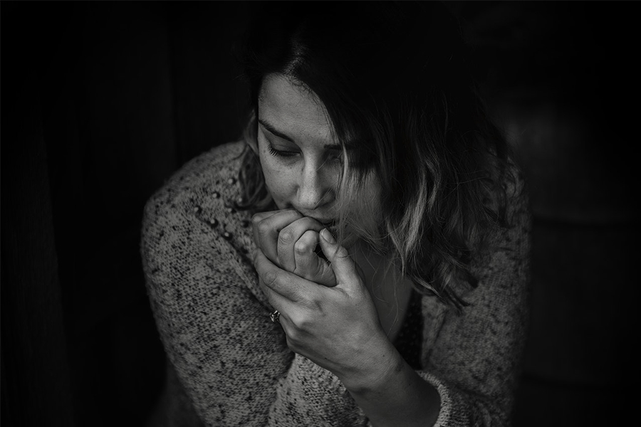 Greyscale photography of women wearing long-sleeved top with hands on her mouth in a thinking position